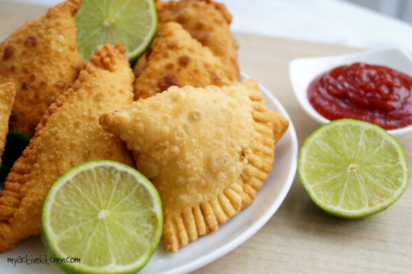 samosa on a white plate with slices of lime and ketchup for dipping